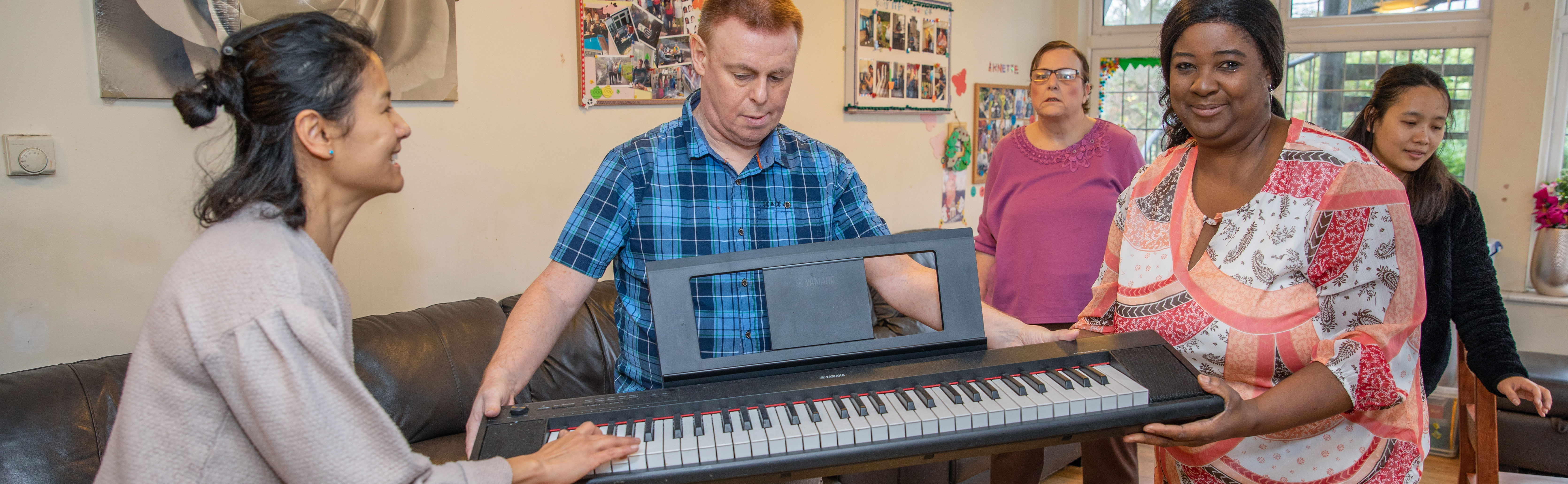 Carers give client keyboard as a present