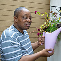 Client watering flowers in hanging baskets