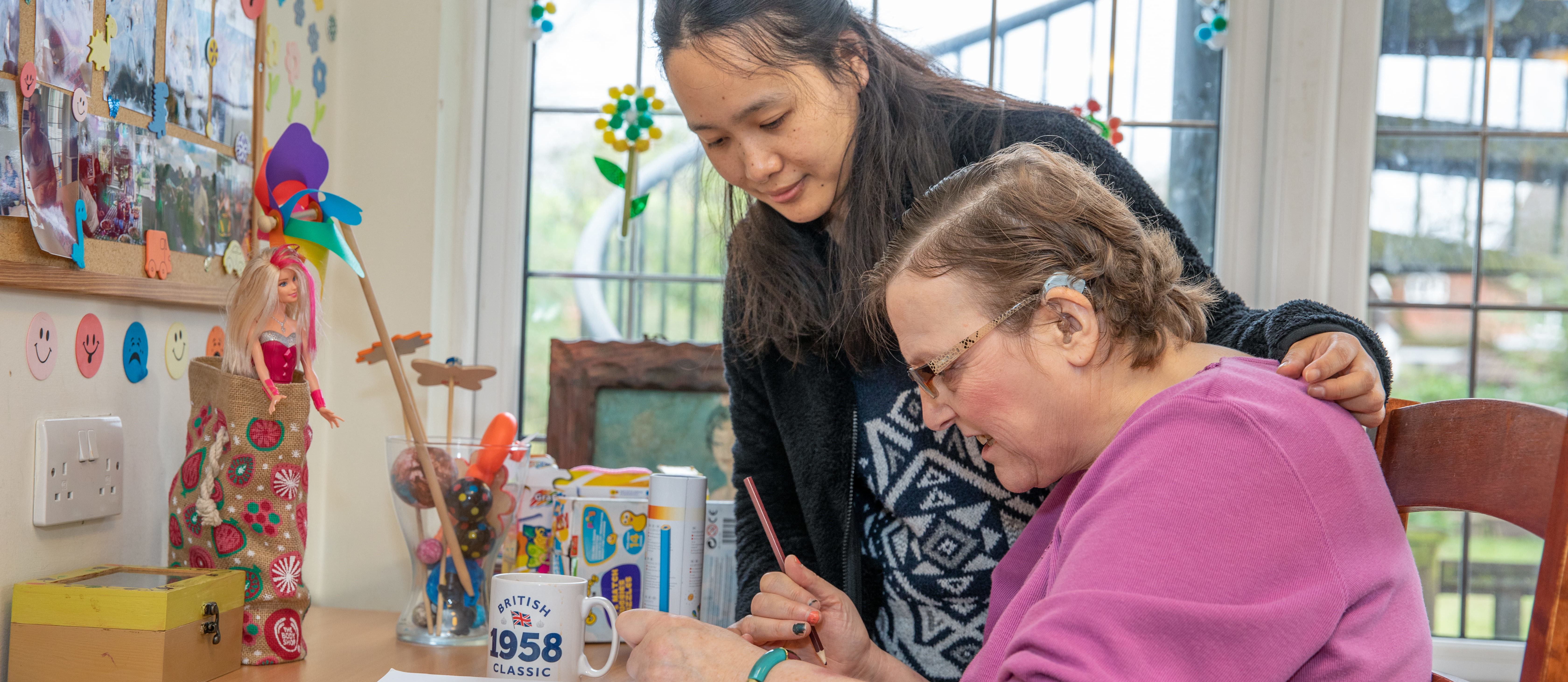 A carer helping a client to draw